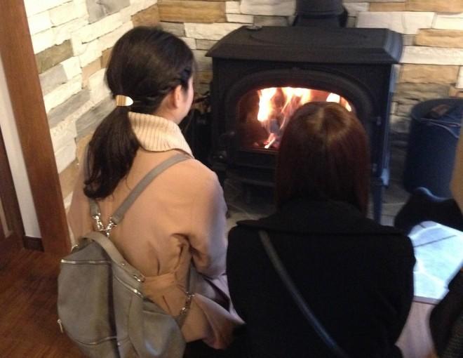 薪ストーブの前で暖をとる人たち