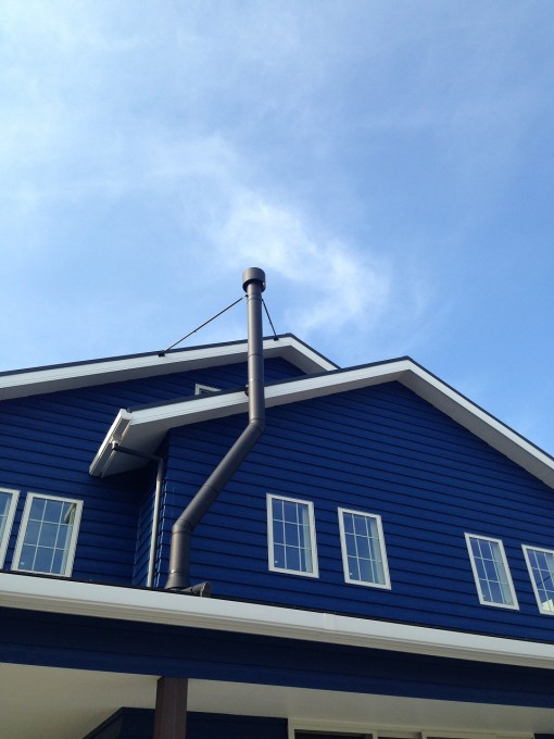 屋根をかわす薪ストーブの煙突